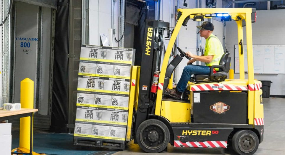 forklift removing boxes from dock truck